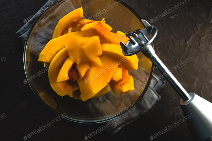 Large pieces of pumpkin in a glass bowl and blender