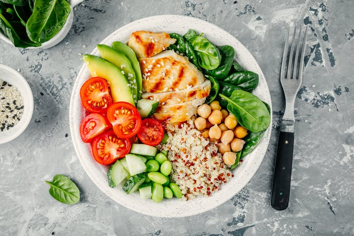 Buddha bowl with spinach, quinoa, chickpeas, grilled chicken, avocado, tomatoes, cucumbers