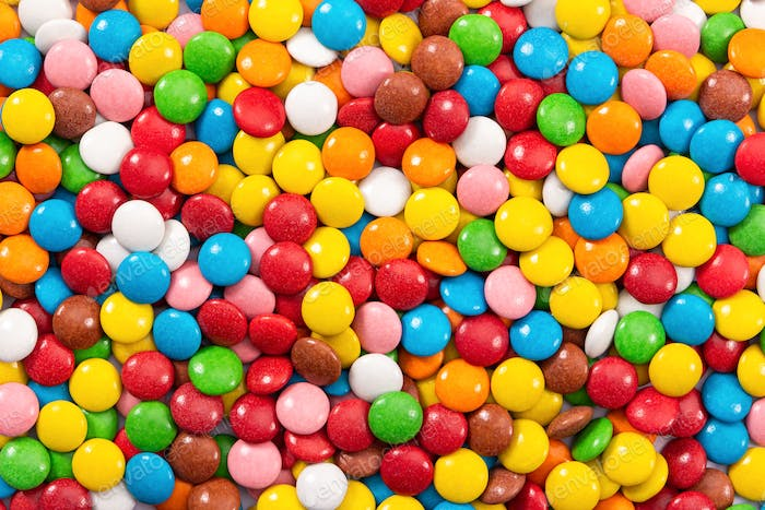 Multicolored button-shaped candies as background