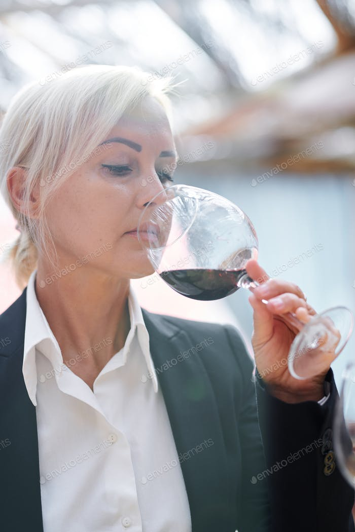 Pretty sommelier checking flavor, smell and quality of red wine