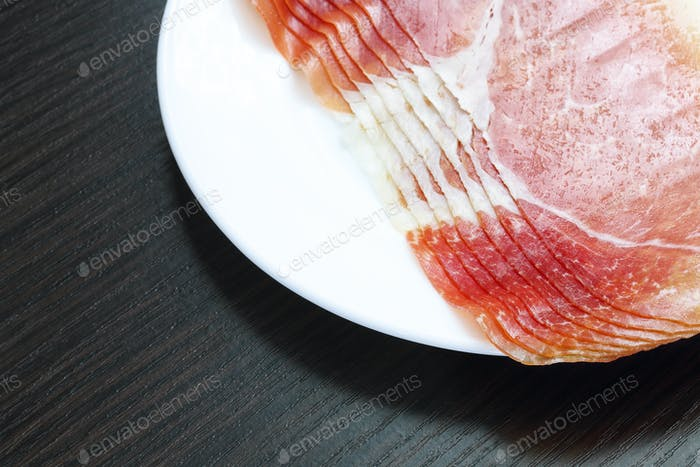 Sliced jamon (hamon) or prosciutto on a wooden background