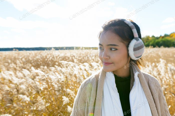 Young beautiful Asian woman thinking and looking away against scenic view of autumn bulrush field