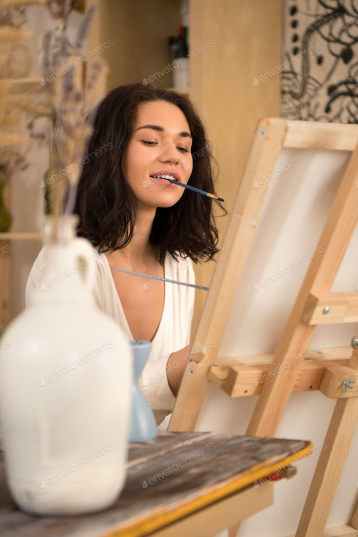 The portrait of happy and beatifull female artist drawing the picture