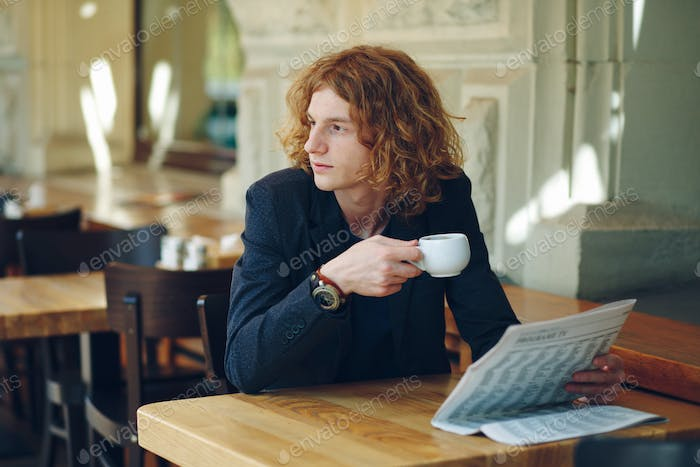 Young reddish man drinking coffee while looking to right