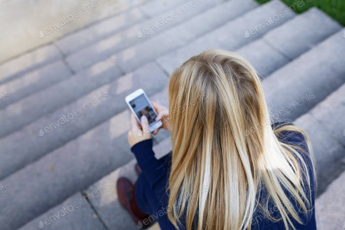 Business Woman Sitting on City Stair Steps and Using Smartphone