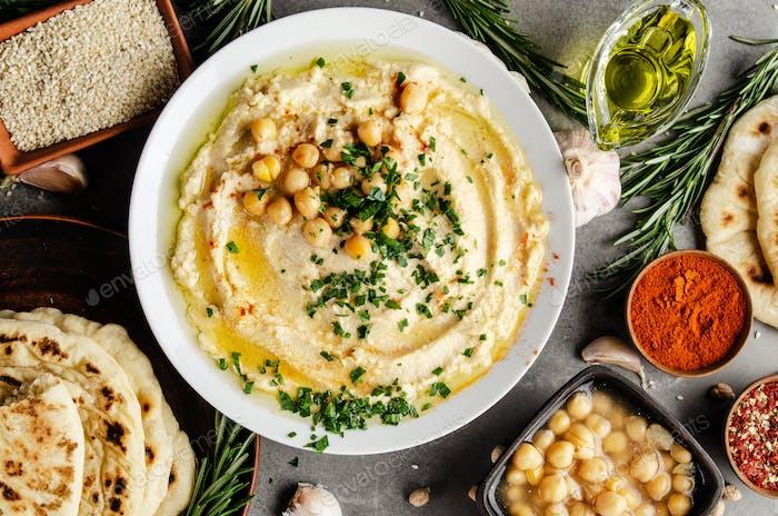 Hummus belegt mit Kichererbsen, Olivenöl und grünen Korianderblättern