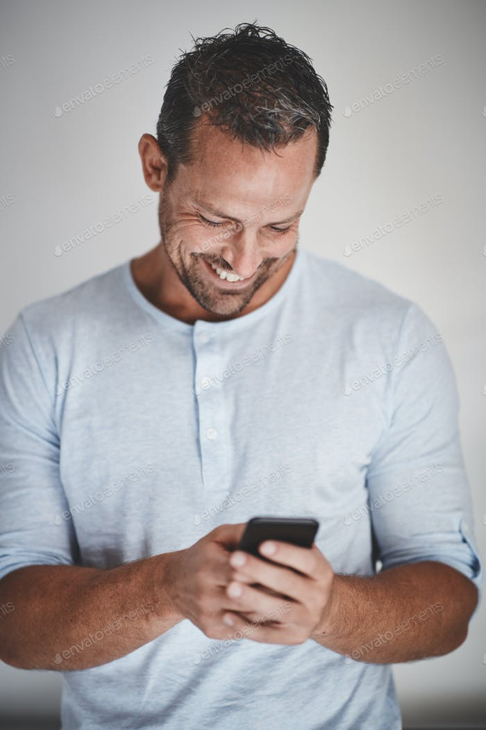 Laughing male entrepreneur standing against a gray background reading texts