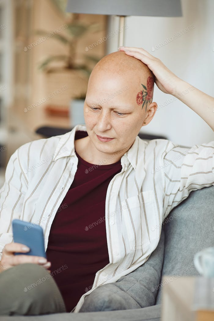 Contemporary Bald Woman Using Smartphone at Home