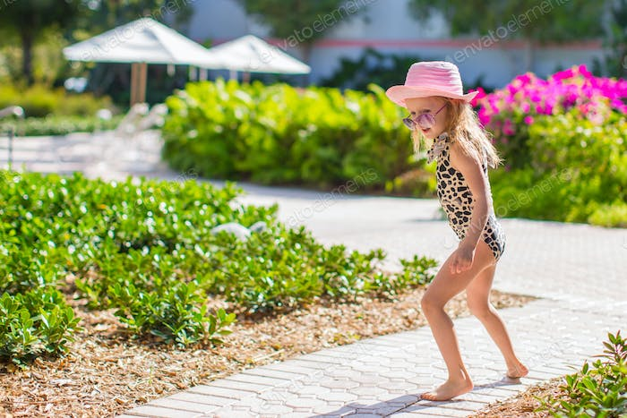 Adorable little girl at hat and swmsuit in exotic resort
