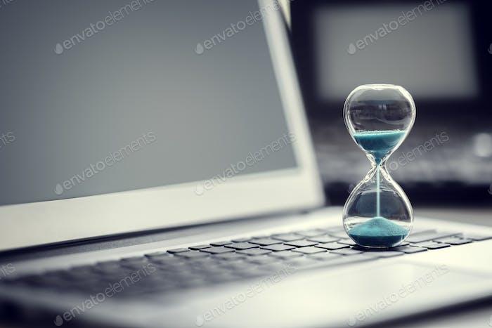 Концепция песочных часов на ноутбуке для управления временем
