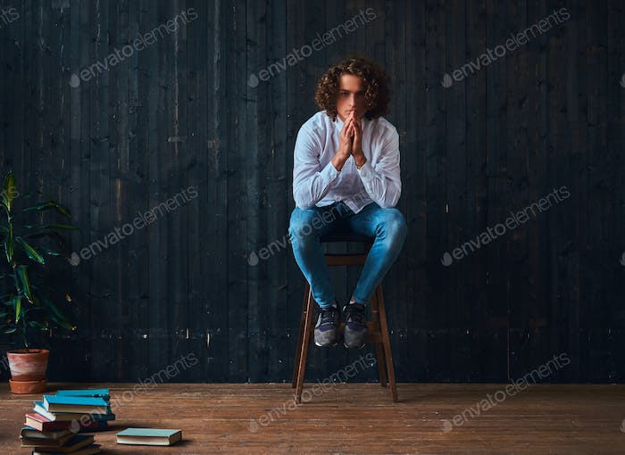 Pensive student holds books while sitting on a chair in a room with minimalist interior.