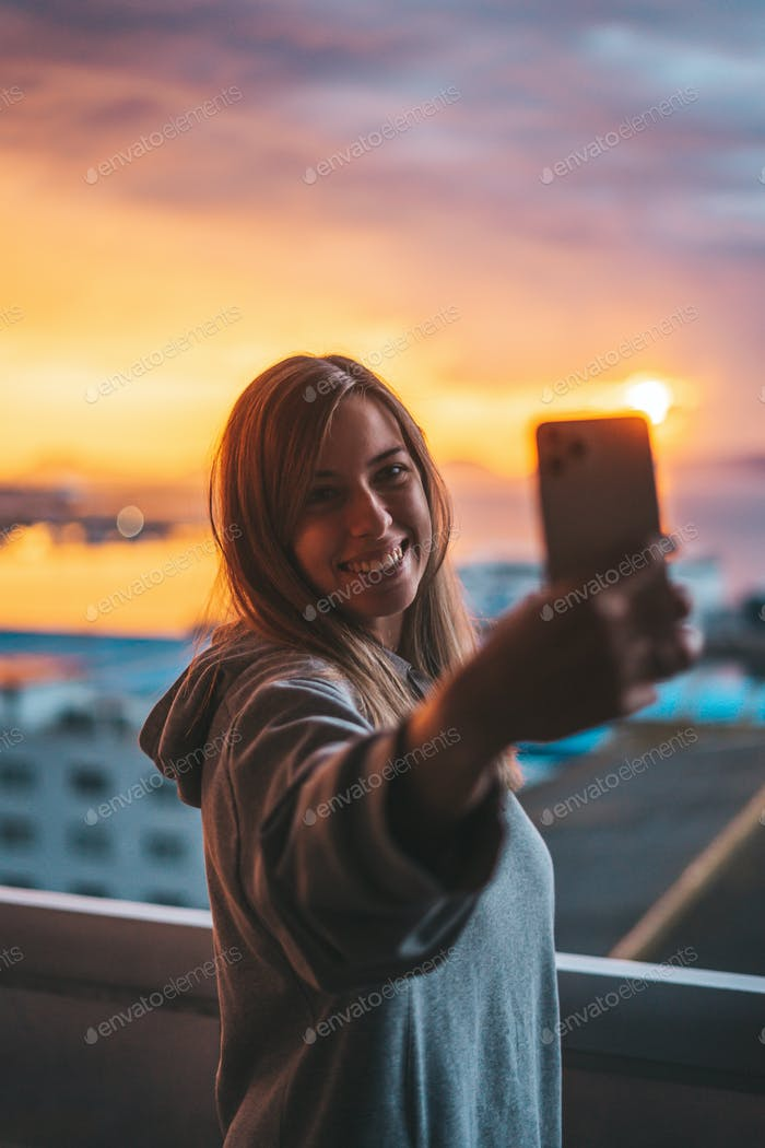 Young woman taking a selfie with the ocean on the background