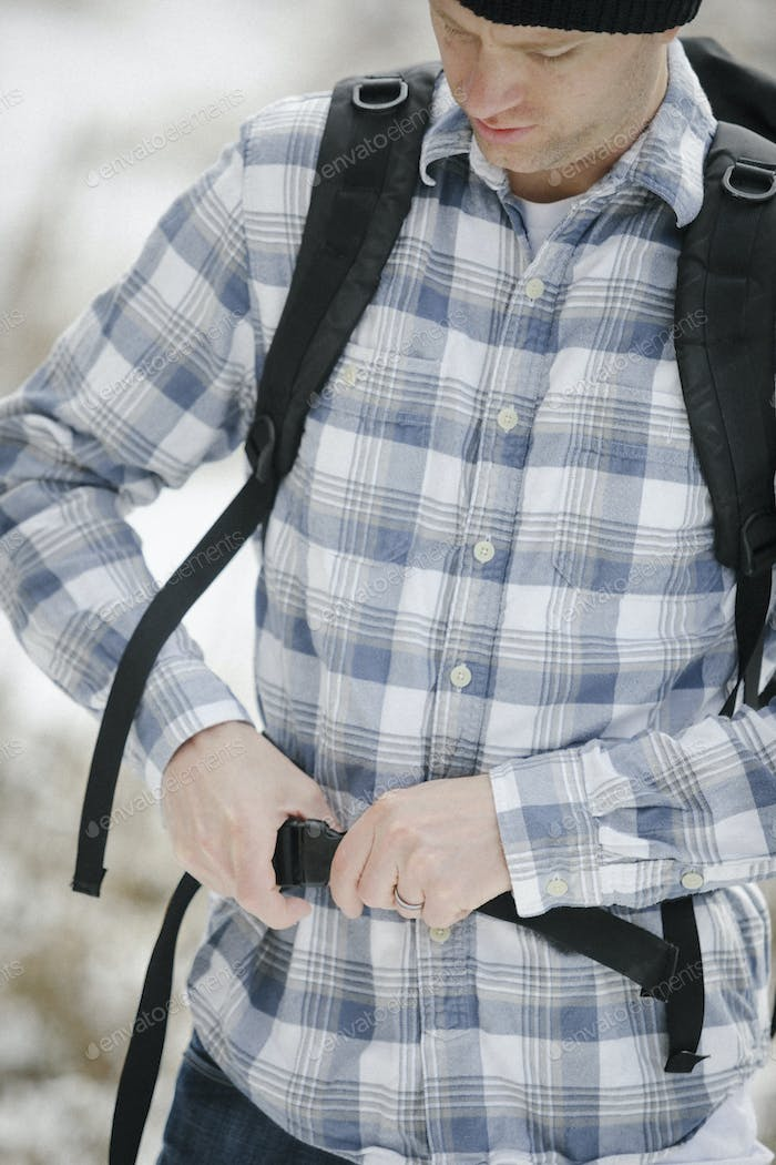 A man, a hiker fastening the belt securing his backpack.