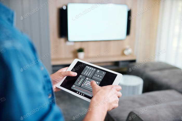 Hands of young man holding tablet with smart remote control system