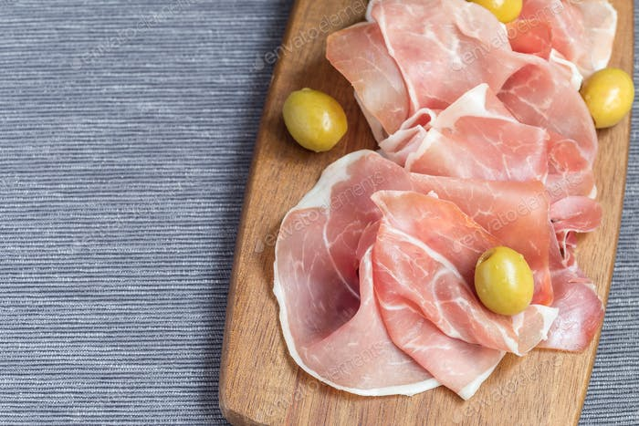 Prosciutto ham with green olives on wooden board, horizontal, co