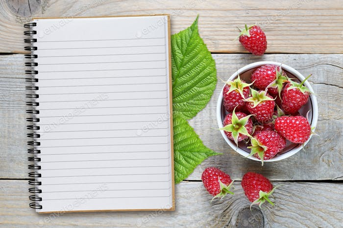 Raspberry and recipe book on wooden table top view