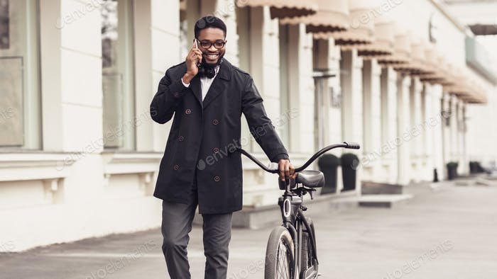 Confident businessman walking with bike and talking on cellphone