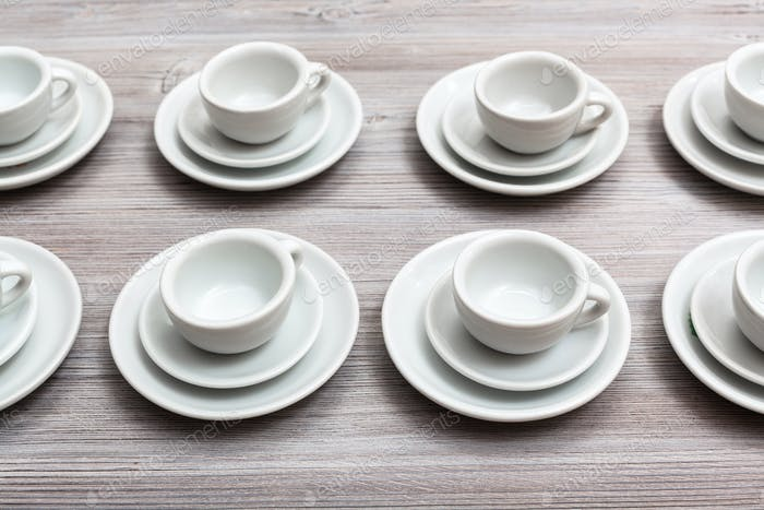 several white cups and saucers on gray brown board