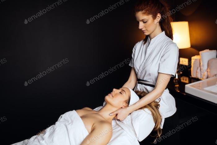 Schöne junge und niedliche Frau genießen Massage-Behandlung