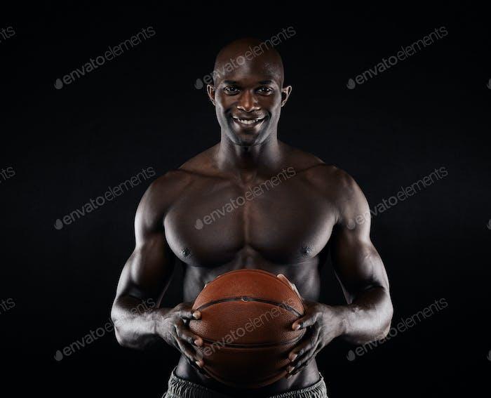 Shirtless Basketballspieler Blick auf Kamera lächelnd.