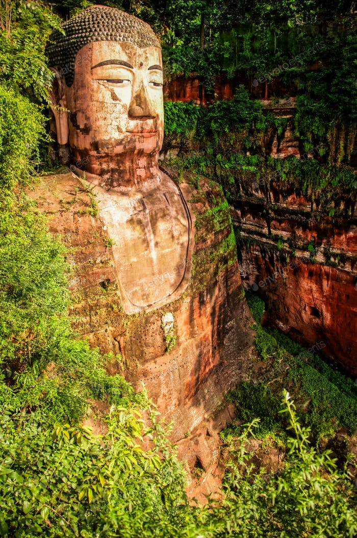 Statue of Leshan Buddha surrounded by green foliage, China