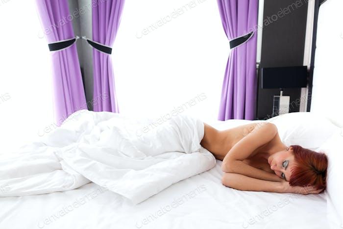 Nackte Frau unter Decke auf Bett liegend