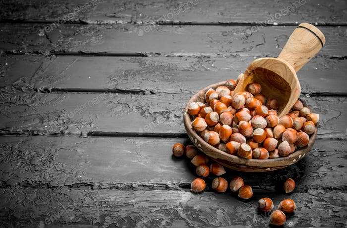 Hazelnuts in a bowl with a wooden scoop.