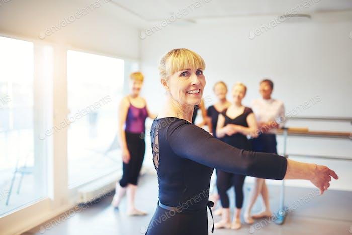 Старшая женщина, практикующая балет в танцевальной студии
