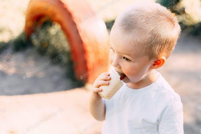 toddler boy eating ice cream in park