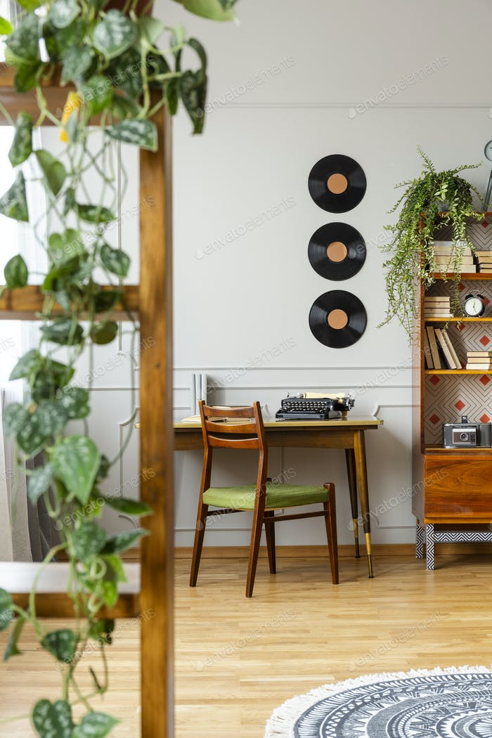 Vinyls above desk with typewriter in stylish vintage apartment