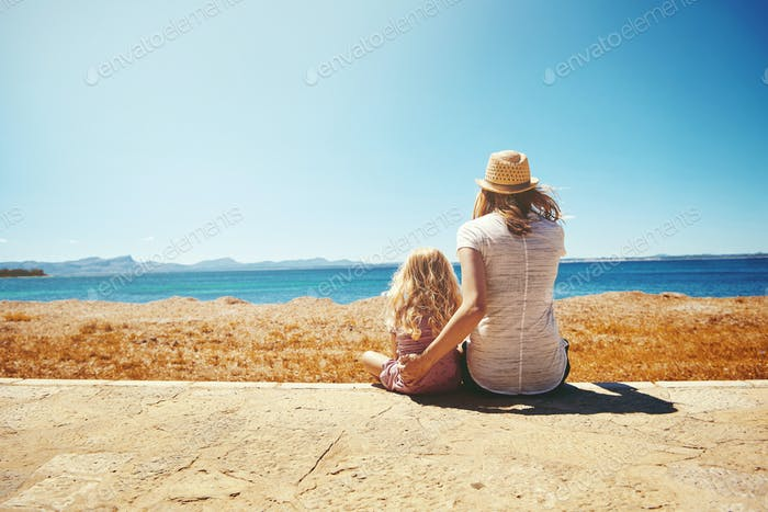 Mother and her daughter sitting on the seashore