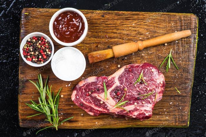 Fleischstück mit Kräutern und Gewürzen auf Holzbrett