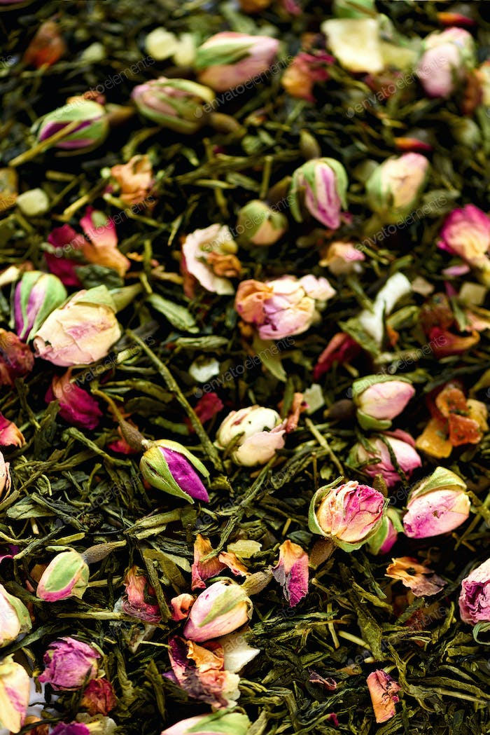 Texture of green tea with rose petals. Dried rosebuds background texture closeup. Food background