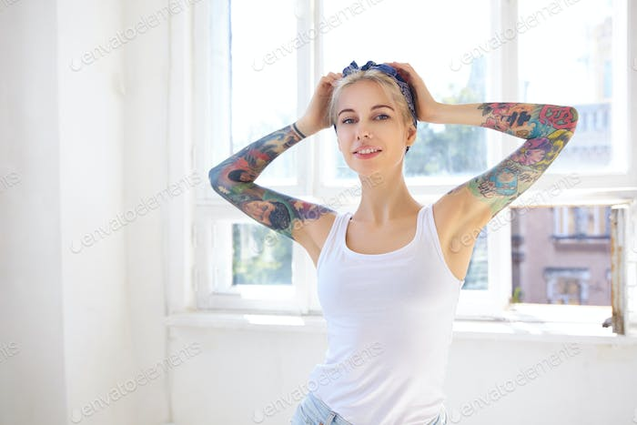 Sunny shot of young attractive tattooed blonde lady keeping raised hands on her head