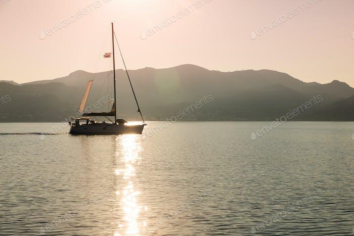 Lonely yacht sailing on silent sea. Aegina Island, Greece