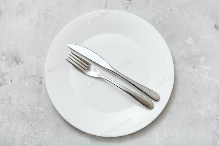 top view of white plate with flatware on concrete