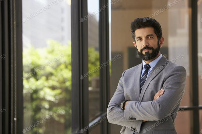 Hispanic businessman with arms crossed looking to camera