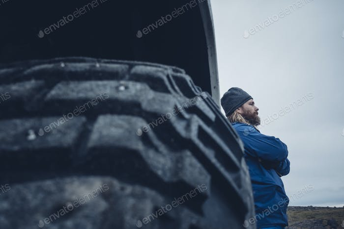 Pensive man leaning on traveling truck