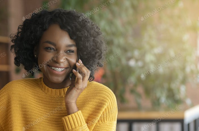 Cheerful afro woman having pleasant conversation by phone