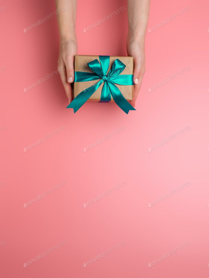 Female hands hold gift box, copy space down
