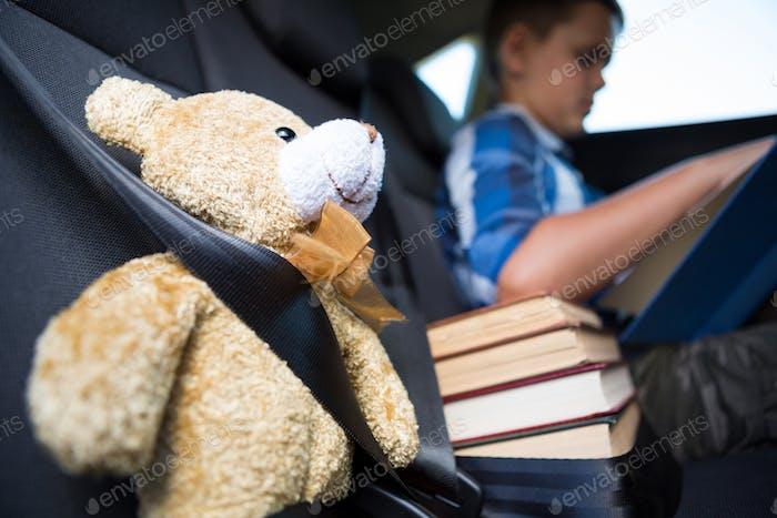 Teenage boy reading book in the car