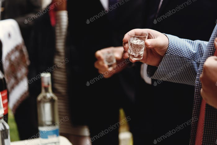 hands of people with  glasses of alcohol, celebrating and toasting, wedding or birthday event