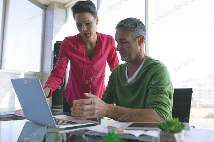 Front view of attentive Multi-ethnic business people discussing over laptop at desk in office