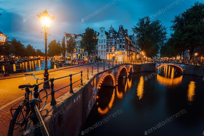 Night city view of Amsterdam. Illuminated bridge on Herengracht canal. Typical dutch houses in hour