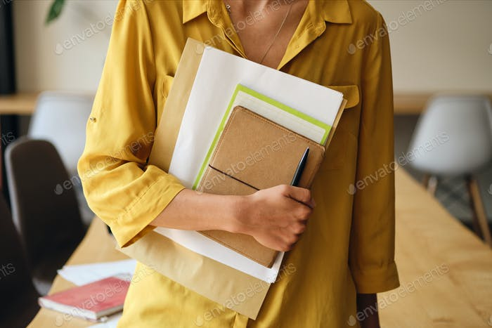 Close up woman in yellow shirt holding notepad and papers in hand in office