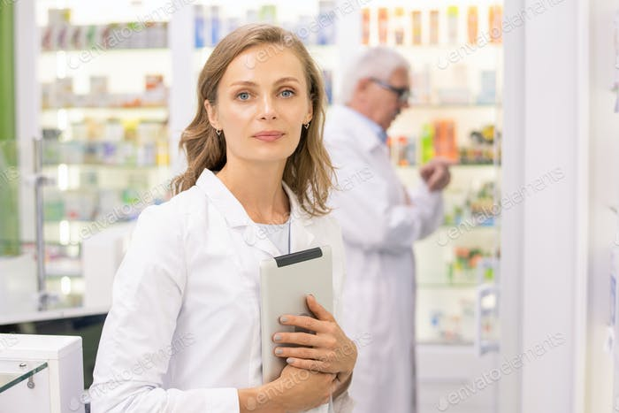 Pretty young pharmacist or worker of contemporary drugstore with digital tablet
