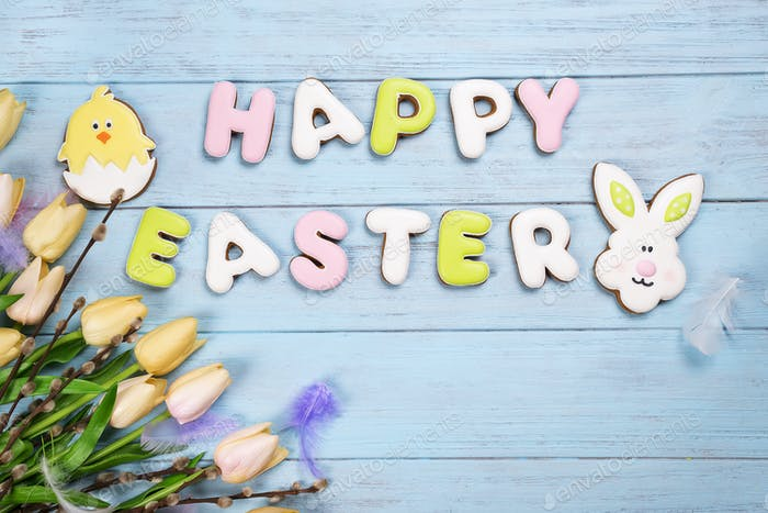 Easter cookies letter Happy Easter with tulips on wood background