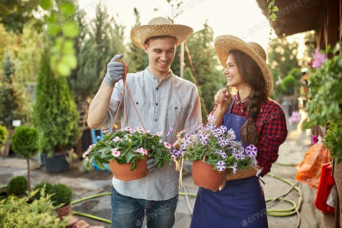 Happy guy and girl gardeners in a straw hats hold pots with petunia on the garden path in on a sunny