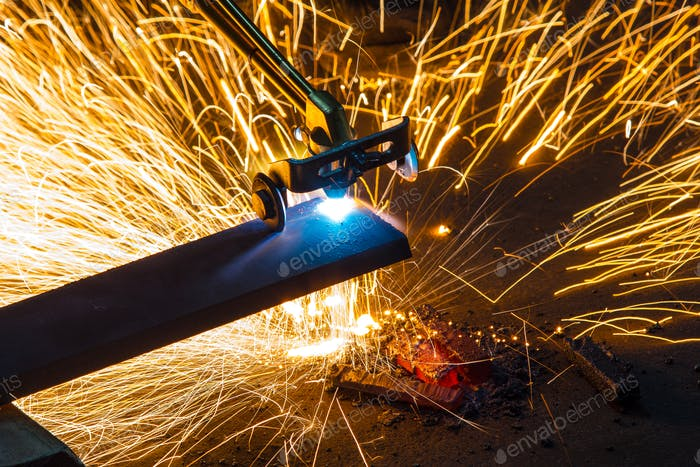 Factory worker cutting metal using acetylene torch