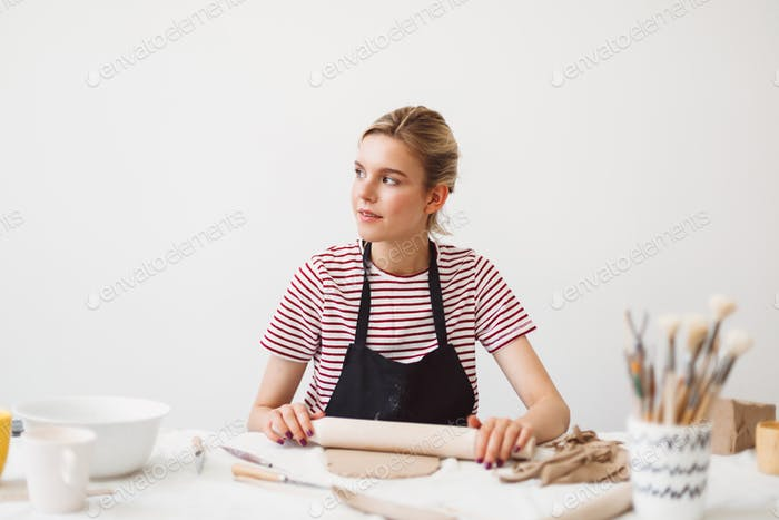 Girl in black apron and striped T-shirt sitting at the table holding rolling pin working with clay